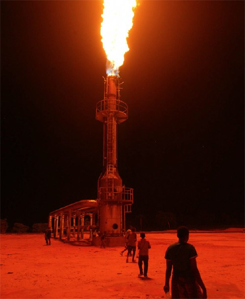 "Children play in the halo of a natural gas flare in Ebocha. The name means ""Place of Light,"" after the flare at an Agip petroleum refinery that has burned there, night and day, since the 1970s.   PHOTO BY MICHAEL KAMBER from Foreign Policy"